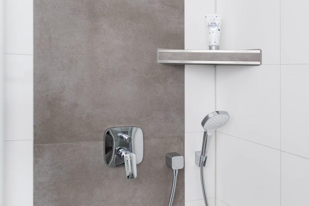 Diese Dusche wird mit edlen Fliesen in Betonoptik belebt. Die eingebaute Duschablage mit Metallabschluss ist dafür wie geschaffen.