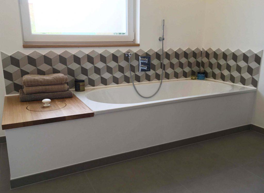 Ausgefallen: Schmucker Fliesendekor mit Würfelmuster und integriertem Stauraum neben der Wanne.
