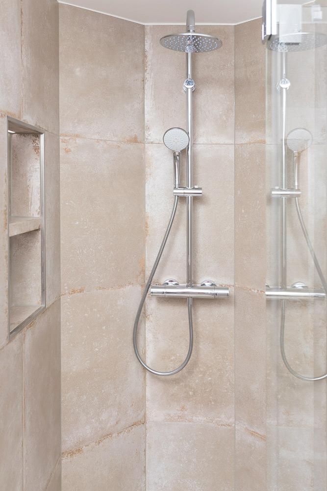 Duschen mit WOW-Gefühl: Abgerundete Dusche im hochwertigen Betonstil mit beleuchteter Wandablage.