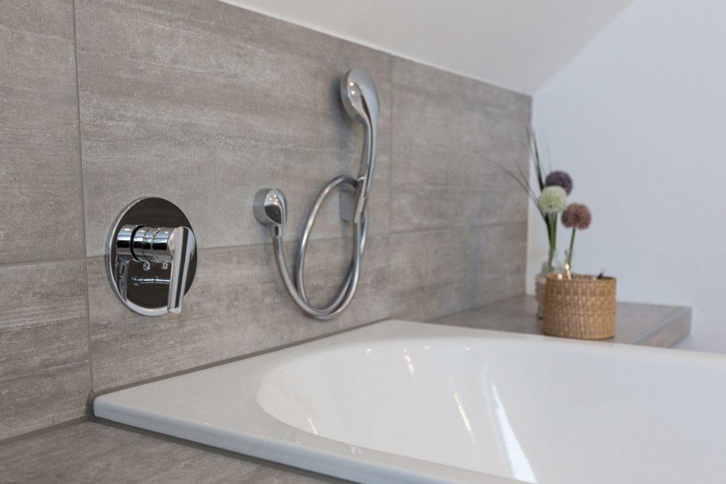 Genussvolles Badevergnügen umgeben von Fliesenplatten in wertvoller Beton-Optik.
