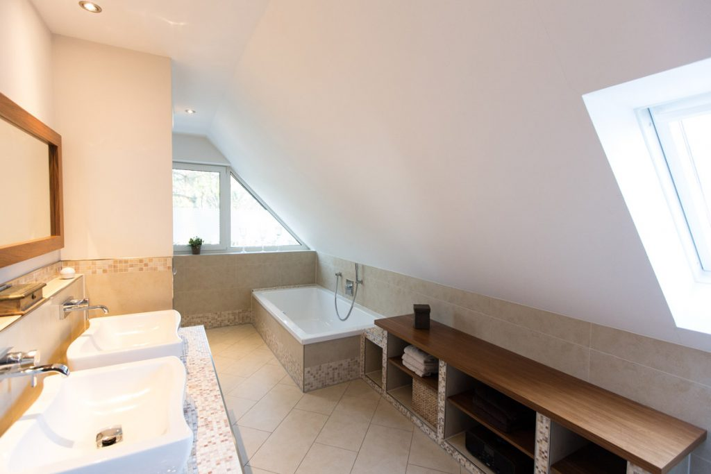 Zu kleines Bad? Gibt's nicht! Unter der Dachschräge ist sogar noch Platz für ein schmuckes Schränkchen aus Mosaik-Fliesen und Holz.