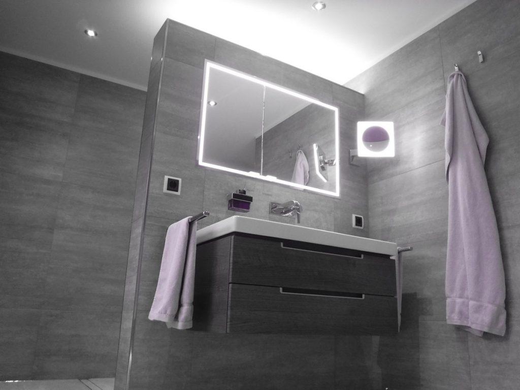 Der Lichtspiegel spendet romantisches Licht und wird durch die anthrazitfarbigen Fliesen gekonnt in Szene gesetzt.
